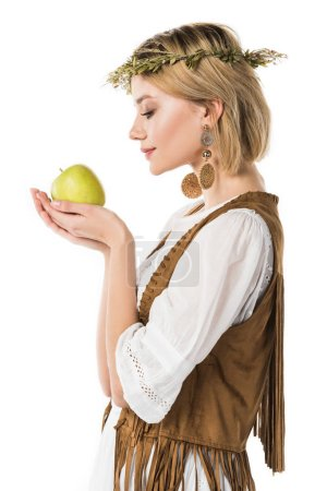 Photo for Side view of charming hippie girl holding green apple isolated on white - Royalty Free Image
