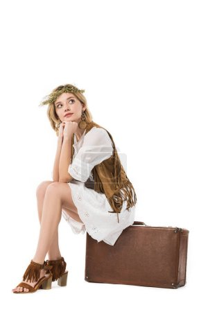 Photo for Pensive attractive boho girl in wreath sitting on suitcase isolated on white - Royalty Free Image