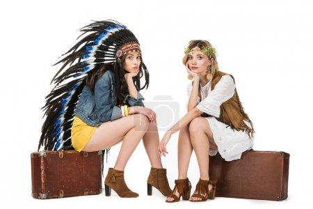 Photo pour Deux filles hippies bisexuelles ennuyées dans la coiffure indienne et la couronne s'asseyant sur des valises d'isolement sur le blanc - image libre de droit