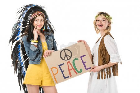 Photo for Two smiling bisexual hippie girls in indian headdress and wreath holding placard with inscription isolated on white - Royalty Free Image