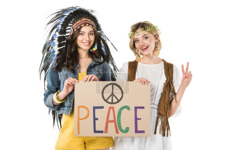 Photo pour Two bisexual hippie girls in indian headdress and wreath holding placard with inscription and showing peace sign isolated on white - image libre de droit