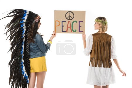 Photo pour Back view of two bisexual hippie girls in indian headdress and wreath holding placard with inscription isolated on white - image libre de droit