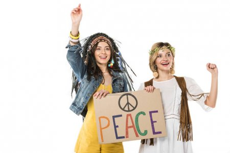 Photo for Two bisexual hippie girls in indian headdress and wreath holding placard with inscription isolated on white - Royalty Free Image