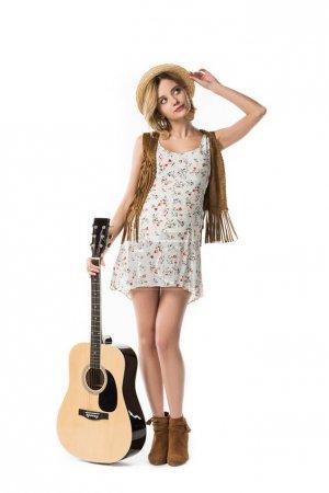 Photo pour Vue pleine longueur de femme de hippie enceinte retenant la guitare acoustique d'isolement sur le blanc - image libre de droit