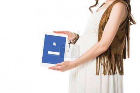 kyiv, Ukraine - 4. Februar 2019: Ausschnittansicht einer schwangeren Frau mit digitalem Tablet und Facebook-App auf dem Bildschirm isoliert auf weiß