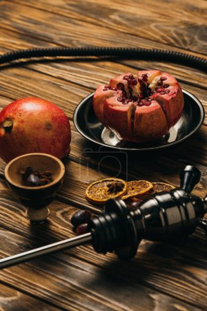 Photo for Hookah, garnets and dried cut oranges on wooden surface - Royalty Free Image