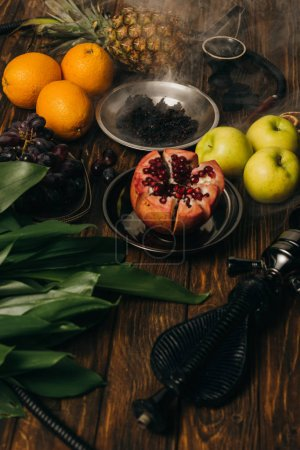 Photo for Hookah, tobacco and exotic fruits on wooden surface - Royalty Free Image