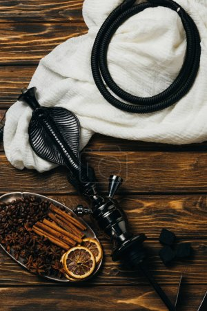 Photo for Top view of cinnamon, dried oranges and hookah on wooden surface - Royalty Free Image