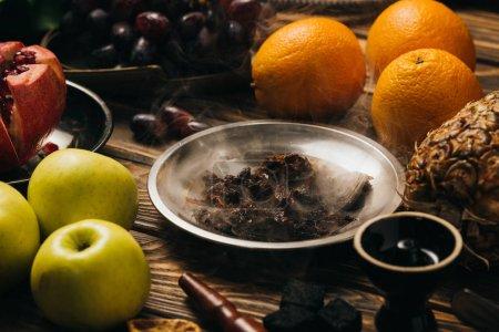 Photo pour Tabac, narguilé, charbons et fruits frais sur la surface en bois - image libre de droit