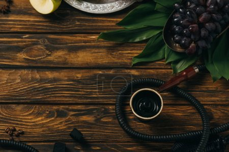 Photo for Top view of hookah, grapes, coffee grains and green leaves on wooden surface - Royalty Free Image