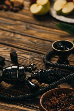 Photo pour Mise au point sélective des pommes, du narguilé, de la cannelle et des charbons sur la surface en bois - image libre de droit