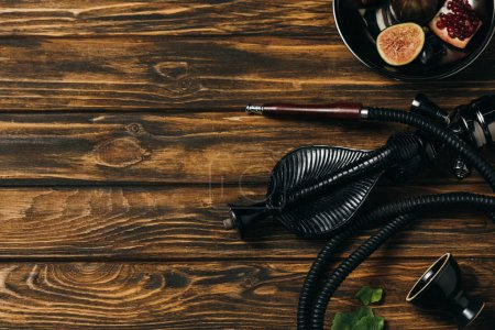 Photo for Top view of hookah and exotic fruits on wooden surface - Royalty Free Image