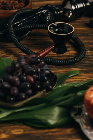 Photo for Selective focus of grapes and hookah on wooden surface - Royalty Free Image