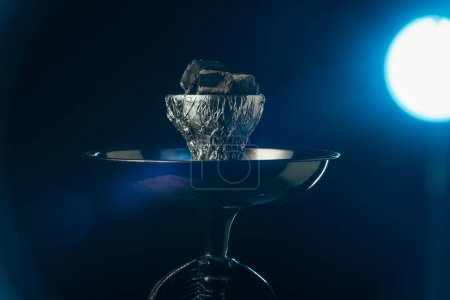Photo for Hookah bowl with coals with blue illumination on black - Royalty Free Image
