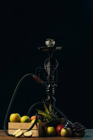 Photo for Fresh tasty fruits and hookah on wooden surface isolated on black - Royalty Free Image