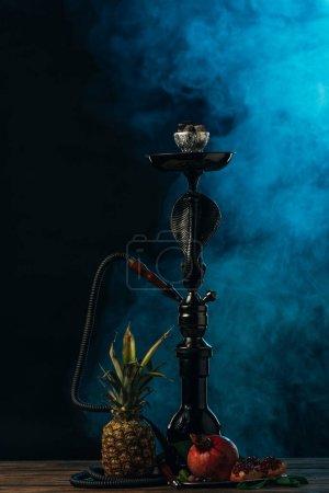 Photo pour Narguilé avec des fruits exotiques sur la surface en bois dans la fumée bleue - image libre de droit