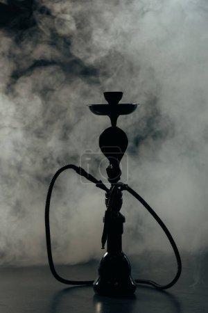 Photo pour Black hookah stem and hose in grey smoke - image libre de droit