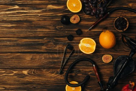 Photo for Top view of fresh fruits, coals and hookah on wooden surface - Royalty Free Image