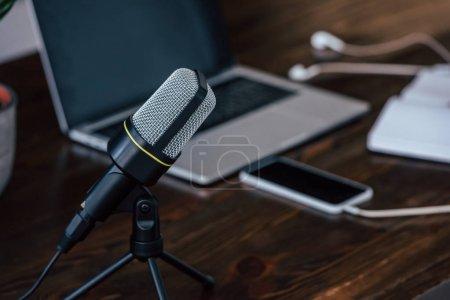 Photo pour Foyer sélectif du microphone près de l'ordinateur portable et smartphone avec écran blanc sur la table en bois - image libre de droit