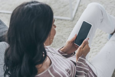 Photo for Overhead view of woman holding smartphone with blank screen - Royalty Free Image