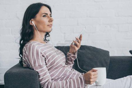 attraktive nachdenkliche Frau, die mit Kopfhörern Musik hört und wegschaut, während sie auf dem Sofa liegt