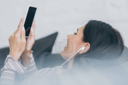 Photo for Selective focus of young woman listening music in earphones while lying on sofa and holding smartphone with blank screen - Royalty Free Image