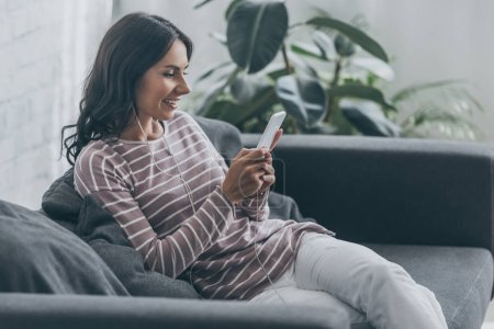 cheerful woman listening music in earphones while sitting on sofa and using smartphone