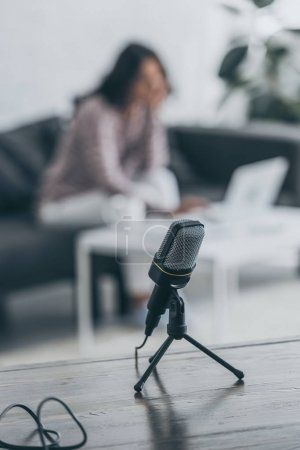 Photo for Selective focus of microphone on wooden tabletop and woman sitting at desk near laptop - Royalty Free Image