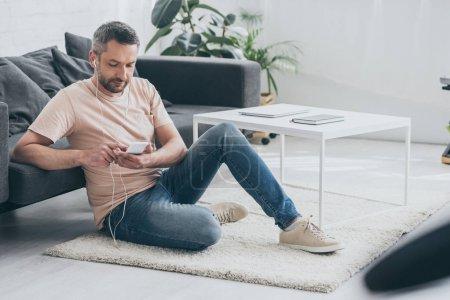 Photo pour Bel homme assis sur le sol à la maison, en utilisant un smartphone et écouter de la musique dans les écouteurs - image libre de droit