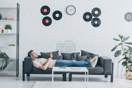 Photo pour Adult man in earphones using smartphone while lying on sofa in spacious living room - image libre de droit