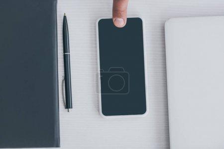 Ausgeschnittene Ansicht des männlichen Fingers auf Smartphone mit leerem Bildschirm in der Nähe von Notebook, Laptop und Stift