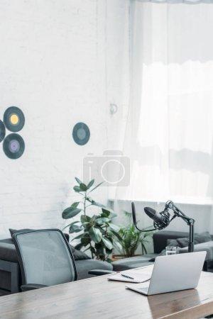 Photo pour Studio de radiodiffusion avec microphone et ordinateur portable sur la table en bois - image libre de droit