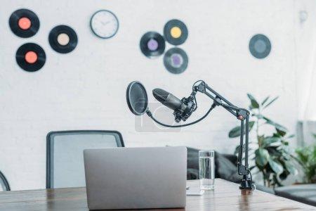 Photo pour Microphone, ordinateur portable et verre d'eau sur le bureau en bois dans le studio de radiodiffusion - image libre de droit