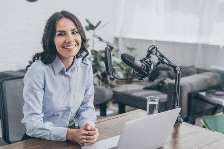 Photo pour Hôte de radio souriant assis sur le lieu de travail près du microphone et regardant la caméra - image libre de droit