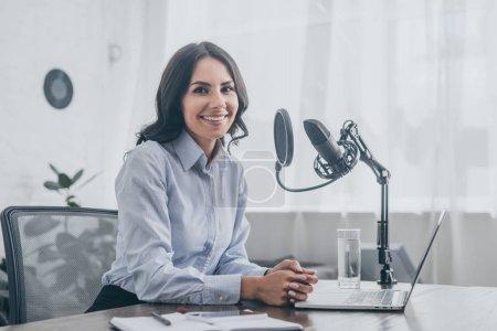 Photo pour Animateur radio joyeux souriant à la caméra tout en étant assis sur le lieu de travail près du microphone - image libre de droit