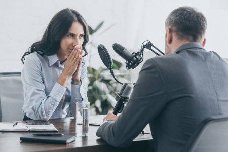Photo pour Animateur de radio attentif itterviewing homme d'affaires dans le studio de radiodiffusion - image libre de droit