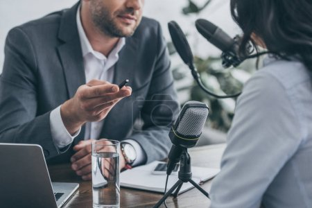 Photo for Cropped view of radio host gesturing while interviewing businesswoman in broadcasting studio - Royalty Free Image