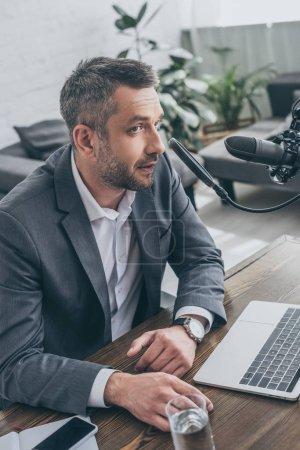 Photo pour Beau animateur de radio parlant au microphone tout en étant assis sur le lieu de travail près d'un ordinateur portable - image libre de droit