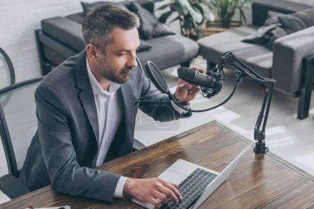 Photo pour Beau hôte radio réglant le microphone et utilisant un ordinateur portable dans le studio de radio - image libre de droit