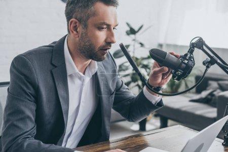 Photo pour Hôte radio grave réglage du microphone tout en étant assis sur le lieu de travail dans le studio de radiodiffusion - image libre de droit