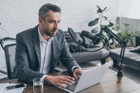 Photo pour Beau hôte radio en utilisant un ordinateur portable tout en étant assis sur le lieu de travail près du microphone - image libre de droit