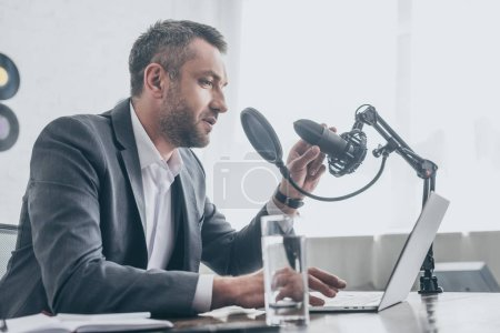 Photo for Handsome radio host speaking in microphone while sitting at workplace near laptop and glass of water - Royalty Free Image
