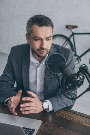 Photo pour Geste grave de l'animateur radio tout en parlant au microphone sur le lieu de travail près d'un ordinateur portable - image libre de droit