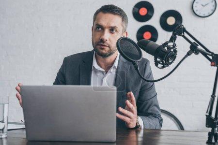Photo pour Beau geste de l'animateur radio tout en parlant au microphone sur le lieu de travail près d'un ordinateur portable - image libre de droit
