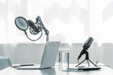 Photo pour Microphones, ordinateur portable et lunettes avec de l'eau sur la table dans le studio de radiodiffusion - image libre de droit