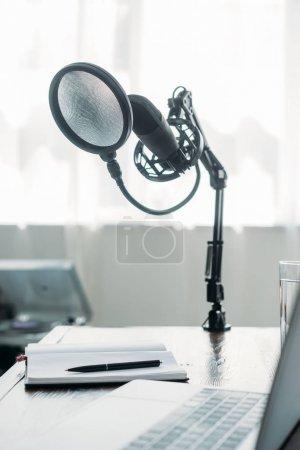Photo pour Foyer sélectif du microphone fixé sur la table près de l'ordinateur portable dans le studio de radiodiffusion - image libre de droit