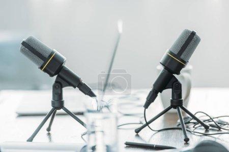 Photo pour Mise au point sélective de deux microphones sur la table en bois dans le studio de radiodiffusion - image libre de droit