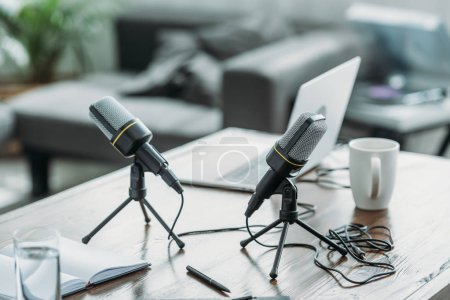 Photo for Two microphones, laptop, notebook and coffee cup on wooden table in radio studio - Royalty Free Image