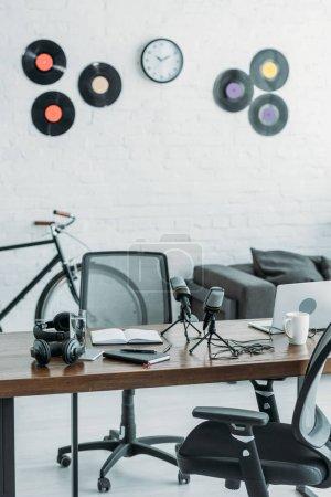 Foto de Furnished broadcasting studio with microphones, laptop and headphones on wooden table - Imagen libre de derechos