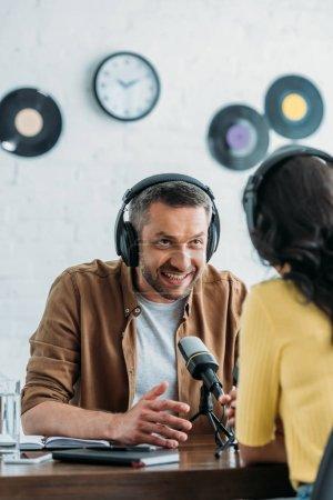 Photo pour Geste d'animateur radio souriant en parlant à un collègue sur le lieu de travail - image libre de droit